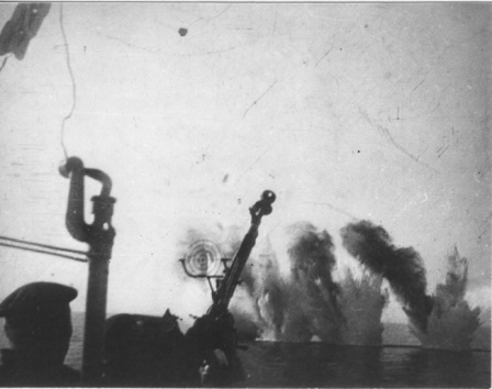 Расчет зенитного пулемета лидера эсминцев «Ташкент» на фоне разрывов от вражеских авиабомб